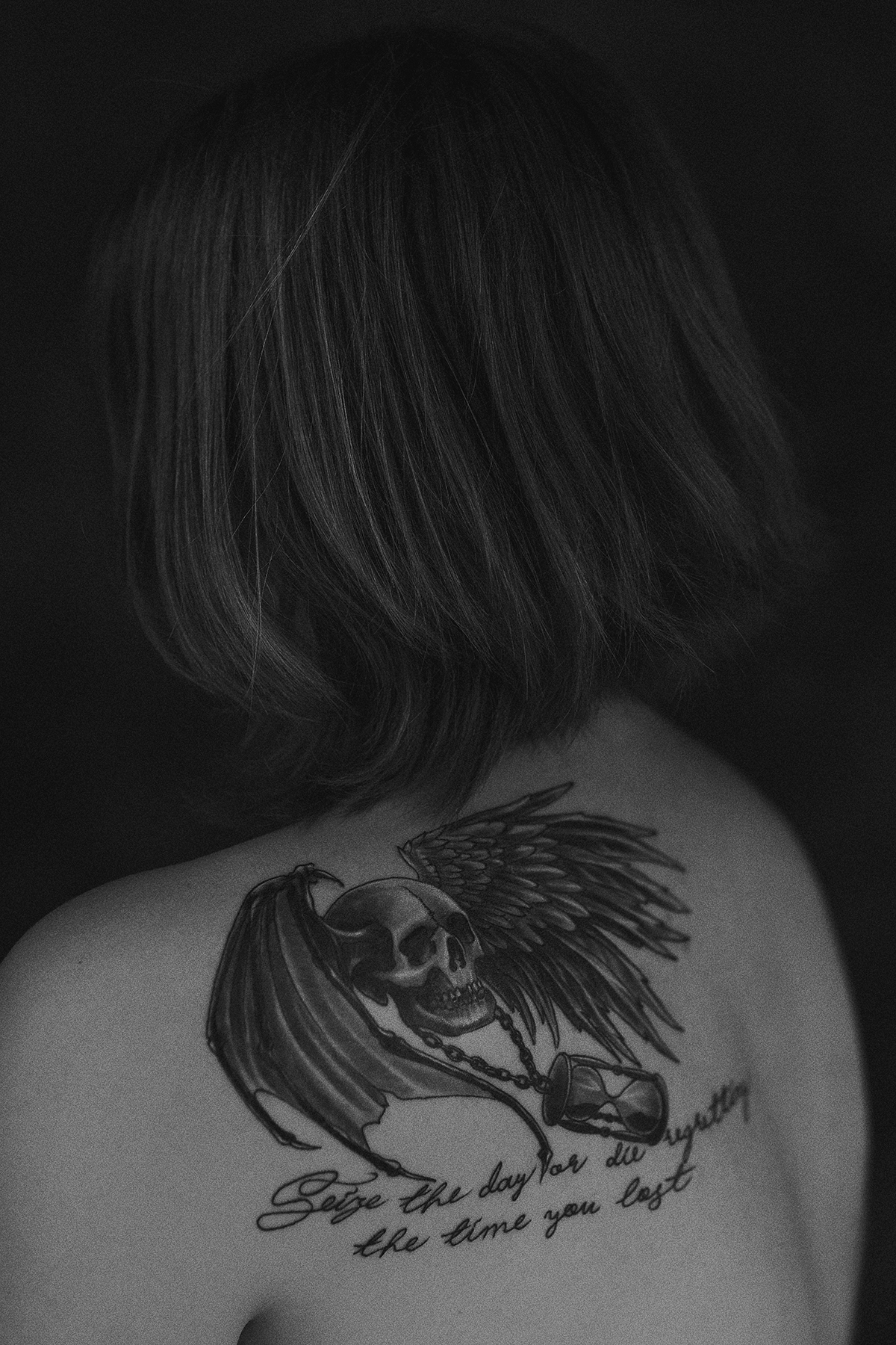 Black and white Portrait of a girl with tattoo on her shoulder; death's head with wings; Seize the day or die regretting the time you lost